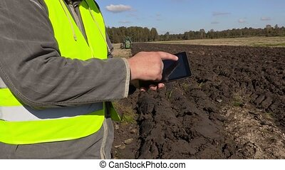 Farmer using tablet on plowed field