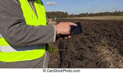 Farmer using tablet on plowed field