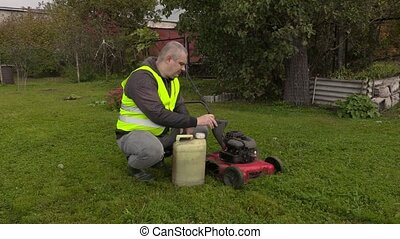 Man fill up petrol on lawn mower