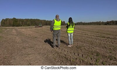 Farmers couple walking away on unplowed field