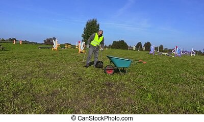 Man with shovel debris collect waste on hurdle field