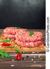 Raw ground beef burgers with chili pepper and arugula on...