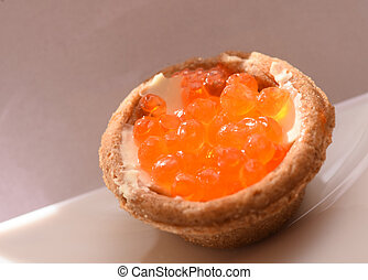 Tartlet with red caviar on a white plate, festive delicacies closeup