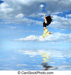 girl jumping against blue sky with water reflection