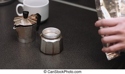 Woman prepares coffee in the kitchen
