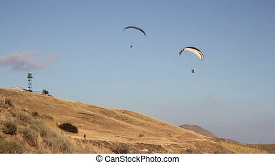 Two paraglider above the bay with mountains