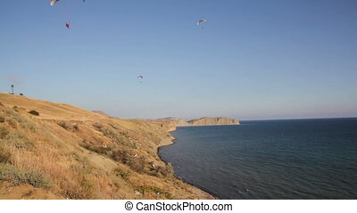 Two paraglider above hills and sea - Two paraglider above...