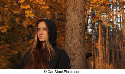 A girl in a hoody with her hair loose standing by a tree in...
