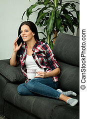 Woman relaxing on her couch with mobile