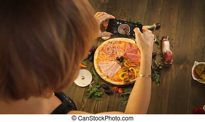 Woman taking a photo of pizza with smartphone