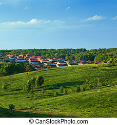Green meadow against blue sky and small town