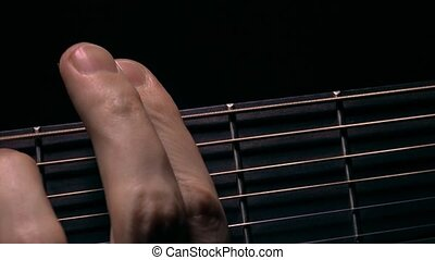 Male hand touching strings on fretboard. Music performance....