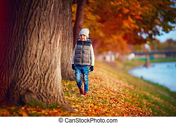 cute fashionable boy walking in autumn park