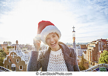 happy traveller woman in Santa hat at Guell Park in...