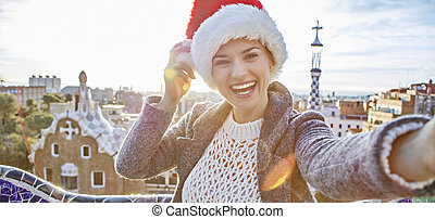 smiling traveller woman in Santa hat at Guell Park taking...