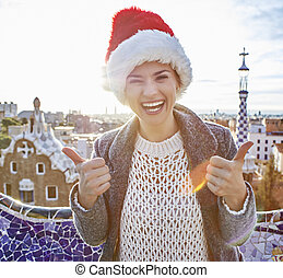 tourist woman in Santa hat at Guell Park showing thumbs up -...