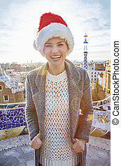 smiling trendy woman in Santa hat at Guell Park in Barcelona...