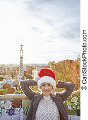 traveller woman in Santa hat at Guell Park relaxing on bench...