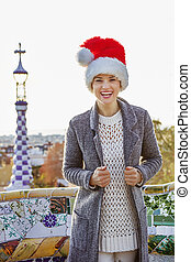 smiling tourist woman in Santa hat at Guell Park in...