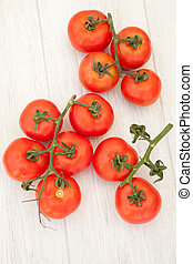 Picture of vine tomatoes on a white wooden background