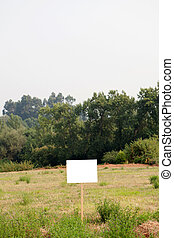 Beautiful meadow with a blank cartel for advertising