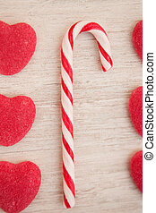Candy canes and heart-shaped candies on a wooden grey...