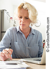 Sitting Woman Concentrates while Calculating Financials on...