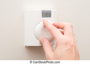 Hand Turning Dial on Wall Mounted Thermostat