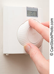Hand Changing Room Temperature with Wall Mounted Thermostat...