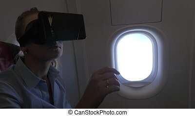 Woman using VR headset in the plane - Slow motion shot of a...
