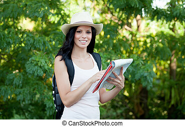 Brunette woman walking through the woods while referring to...