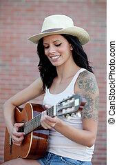 Brunette pretty woman playing a guitar - Brunette pretty...