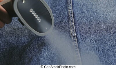 Woman steaming denim fabric on ironing table - Woman...
