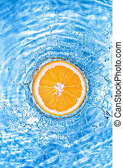 Fresh orange dropped into water with bubbles isolated on...