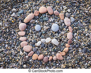 Stone sad face on beach