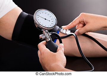 Doctor Checking Blood Pressure Of Patient - Close-up Of A...