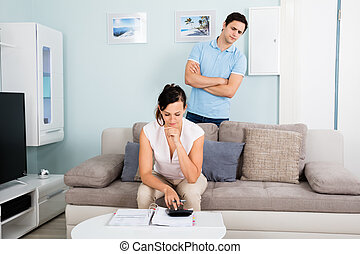 Suspicious Man Looking At Bills From Behind His Wife