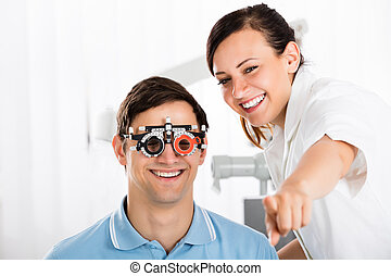 Optometrist Examining Patient's Vision With Trial Frame