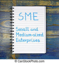 SME- Small And Medium-sized Enterprises acronym written in notebook on wooden background