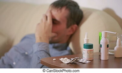 sick man lying in bed suffering virus having medicine...