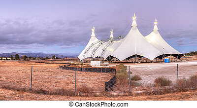 Sunset over a circus tent in a large field in summer.