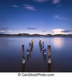 Wooden pier or jetty remains on a blue lake sunset and sky reflection on water. Versilia Tuscany, Italy