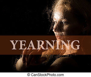 yearning written on virtual screen. hand of young woman melancholy and sad at the window in the rain