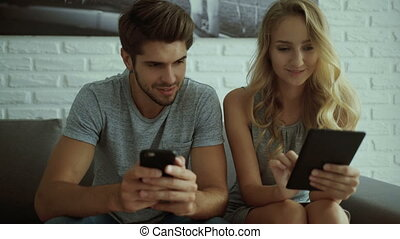 Young man showing news on his phone, while girlfriend using tablet.
