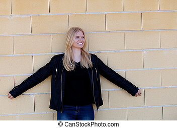 Pretty blonde single woman portrait outdoors with a wall of...