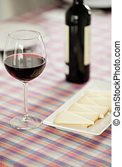 Glasses of red wine and cheese tray on a table with...