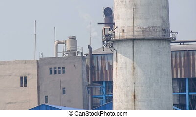 Factory chimney emitting gas in air, polluting environment....