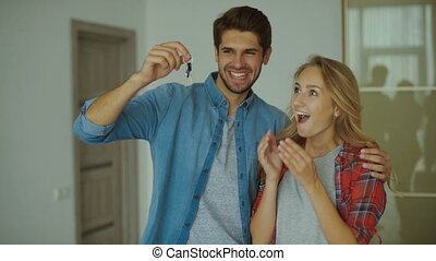Happy couple holding a key of new apartment.