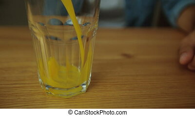 Pouring orange juice into glass shooting with high speed...