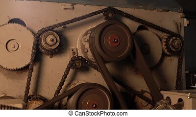 Close-up view of rotating gears on running machine -...